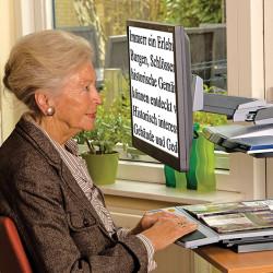 Frau liest mit Bildschirmlesegerät von Optelec Vergrößernde Sehhilfe Optik Plüschke Bischofswerda