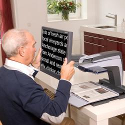 Mann liest mit Bildschirmlesegerät von Optelec Vergrößernde Sehhilfe Optik Plüschke Bischofswerda