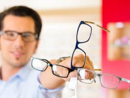 junger Mann mit mehreren Brillen in der Hand